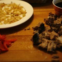 Toisen päivän raaka-aineita: Chilipaprikaa, paahdettuja sipuleita sekä valkosipulia sekä itse porsaan niska sooseineen.